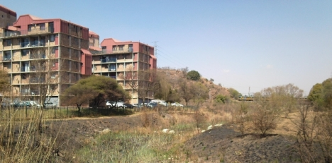 Hartbees Spruit, looking south towards the Colbyn Wetlands, with a train passing through. North Shore flats on the left