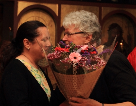 Anthia Falekkos gives Val Hayes a bunch of flowers on behalf of the parish of St Nicholas